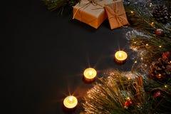 圣诞节礼物,圣诞树,蜡烛,上色了装饰,星,在黑背景的球 免版税库存图片