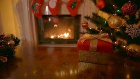圣诞节礼物移动式摄影车射击在红色箱子的有在客厅的金黄弓的有灼烧的壁炉的 股票视频