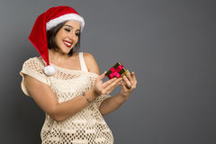 圣诞节礼物-妇女开头礼物惊奇的和愉快,年轻b 免版税库存图片