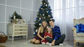 圣诞节系列愉快的最近的结构树 愉快的拥抱和亲吻在圣诞树附近的妈妈爸爸和女儿 免版税图库摄影