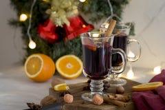 圣诞节红色在玻璃的加香料的热葡萄酒在木委员会在白色背景 库存图片