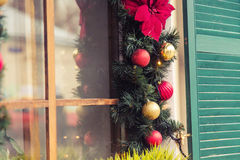 圣诞节红色球装饰了在葡萄酒房子的窗口 免版税库存照片