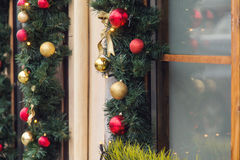 圣诞节红色球装饰了在葡萄酒房子的窗口 免版税图库摄影