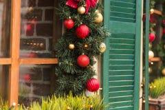圣诞节红色球装饰了在葡萄酒房子的窗口 库存图片