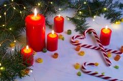 圣诞节红色蜡烛和轻神仙在微明下 免版税图库摄影