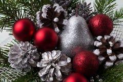 圣诞节红色装饰品、银色杉木锥体和闪烁梨 库存照片