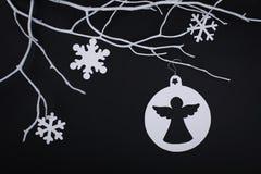 圣诞节纸天使和垂悬在blac的雪花装饰 图库摄影