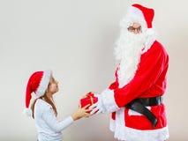圣诞节给女孩的圣诞老人当前 库存照片