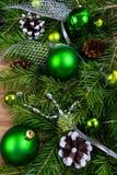 圣诞节绿色中看不中用的物品、杉木锥体和银小珠赃物 库存图片