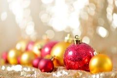 圣诞节背景、新年关闭红色和金装饰球在闪烁摘要弄脏了假日bokeh背景 免版税图库摄影