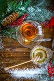 圣诞节背景、茶用蜂蜜和新月形面包,一棵圣诞树的分支在雪的 图库摄影