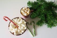 圣诞节背景、贺卡与一杯咖啡或巧克力用蛋白软糖,棒棒糖、一块红色板材和树枝 免版税库存图片