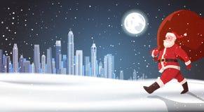 圣诞节背景圣诞老人运载袋子在夜冬天城市风景假日概念的礼物 库存照片