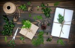 圣诞节背景用手制作了礼物,在土气木桌上的礼物 圣诞节DIY包装 顶上,平的位置,顶视图 免版税库存照片