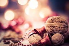 圣诞节背景用核桃、红色响铃和蜡烛 免版税库存图片