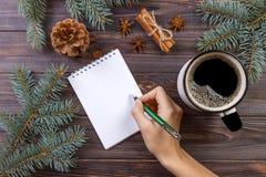圣诞节背景:写在有拷贝空间的被打开的笔记本的女性手在用圣诞节得体盖的土气木桌 库存照片