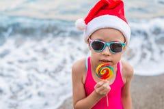 圣诞节背景:圣诞老人帽子的逗人喜爱的孩子庆祝新年和圣诞节在海滩的,自由空间 免版税库存图片