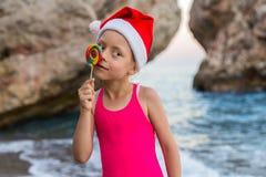 圣诞节背景:圣诞老人帽子的逗人喜爱的孩子庆祝新年和圣诞节在海滩的,自由空间 免版税库存照片