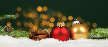 圣诞节背景-圣诞节球和肉桂条有杉木分支的在雪与被弄脏的光 库存图片