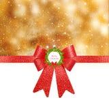 圣诞节背景-在金黄背景的红色弓 免版税图库摄影