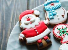 圣诞节自创姜饼曲奇饼,在板材的香料在圣诞礼物中的黑暗的木背景,顶视图 库存图片