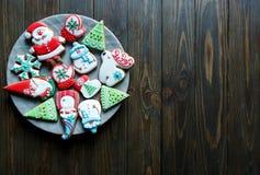圣诞节自创姜饼曲奇饼,在板材的香料在圣诞礼物中的黑暗的木背景 免版税库存照片