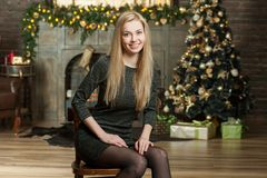 圣诞节舒适内部的少妇  女孩坐在许多礼物中的一棵圣诞树下 为圣诞节做准备 布加勒斯特c e办公室 库存图片