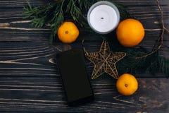 圣诞节舱内甲板在圣诞节backgrou放置有空的屏幕的电话 免版税库存图片