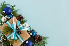 圣诞节舱内甲板在蓝色背景放置冷杉与拷贝空间的分支和装饰的构成与礼物盒的 免版税库存照片