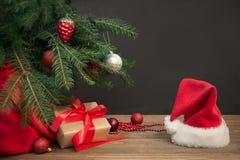 圣诞节节假日背景 与一个红色丝带,圣诞老人` s帽子和装饰的礼物在一个木板的一棵圣诞树下 免版税库存图片