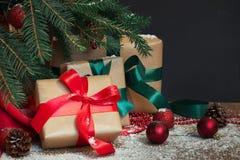 圣诞节节假日背景 与一个红色丝带,圣诞老人` s帽子和装饰的礼物在一个木板的一棵圣诞树下 库存图片