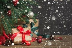 圣诞节节假日背景 与一个红色丝带,圣诞老人` s帽子和装饰的礼物在一个木板的一棵圣诞树下 库存照片