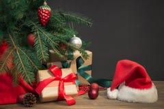 圣诞节节假日背景 与一个红色丝带,圣诞老人` s帽子和装饰的礼物在一个木板的一棵圣诞树下 免版税库存照片