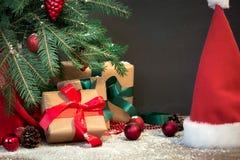 圣诞节节假日背景 与一个红色丝带,圣诞老人` s帽子和装饰的礼物在一个木板的一棵圣诞树下 复制空间 免版税库存照片