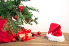 圣诞节节假日背景 与一个红色丝带,圣诞老人` s帽子和装饰的礼物在一个木板的一棵圣诞树下 复制空间 库存照片