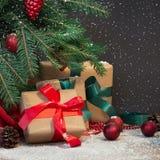 圣诞节节假日背景 礼物,圣诞老人` s盖帽和装饰在一棵圣诞树下在一个木板 复制在黑板的空间 库存图片