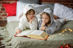 圣诞节节假日 兄弟和姐妹在软的睡衣的一张床放置 库存图片