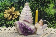 圣诞节节假日 金黄杉木锥体,圣诞树玩具,蜡蜡烛,演奏长笛,反对b的紫晶的天使的图 免版税库存图片