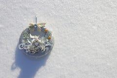 圣诞节花圈在新鲜的雪的阳光下 库存照片