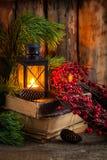 圣诞节花圈用在旧书的莓果与在木背景的一个灯笼 库存照片