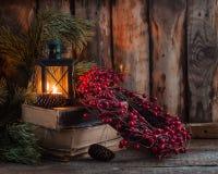 圣诞节花圈用在旧书的莓果与在木背景的一个灯笼 免版税库存图片