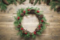 圣诞节花圈由云杉的分支做成用霍莉莓果在木板 平的位置 顶视图 免版税图库摄影