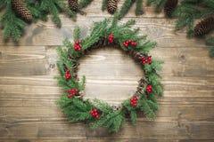 圣诞节花圈由云杉的分支做成用霍莉莓果在木板 平的位置 顶视图 免版税库存图片