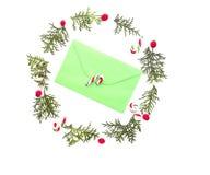 圣诞节花圈由金钟柏枝杈制成,与绿色的红色狂放的玫瑰色果子在中部包围和棒棒糖 空白 免版税库存图片