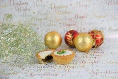 圣诞节花食物摄影与闪烁的在xmas包装纸背景的肉馅饼中看不中用的物品 库存照片