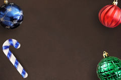 圣诞节蓝色,红色,波浪和绿色有肋骨球,在黑暗的木桌上的棍子 免版税库存照片