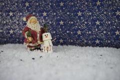 圣诞节蛋白软糖的食物照片在背景中塑造了,在雪的雪人与特征模式与圣诞老人装饰 免版税库存照片