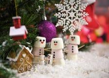 圣诞节蛋白软糖食物摄影塑造了作为在雪的雪人在与装饰的一棵圣诞树下 免版税库存照片