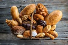 圣诞节蛋糕、卷和面包在篮子在木桌上,背景面包店的或市场 免版税库存照片