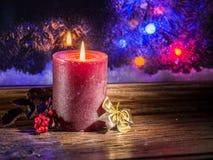 圣诞节蜡烛光和冻窗口 免版税库存照片